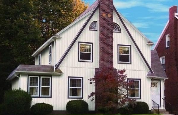 Вертикальный сайдинг на двухэтажном строении с нестандартной архитектурой