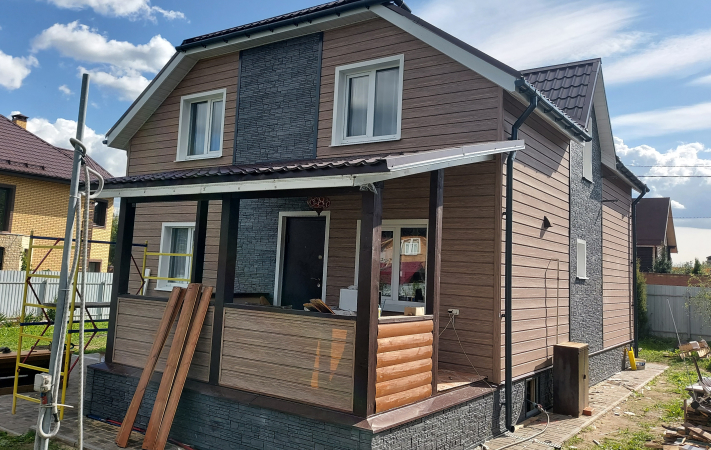 Дом после облицовки фасадными панелями и виниловым сайдингом Docke